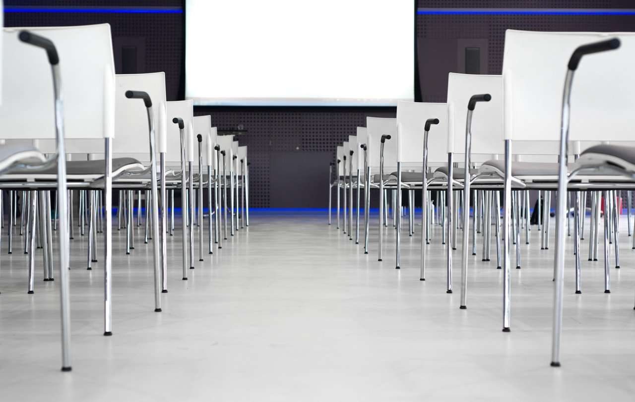 auditorium with white plastic chairs get tons of attendees at your next webinar