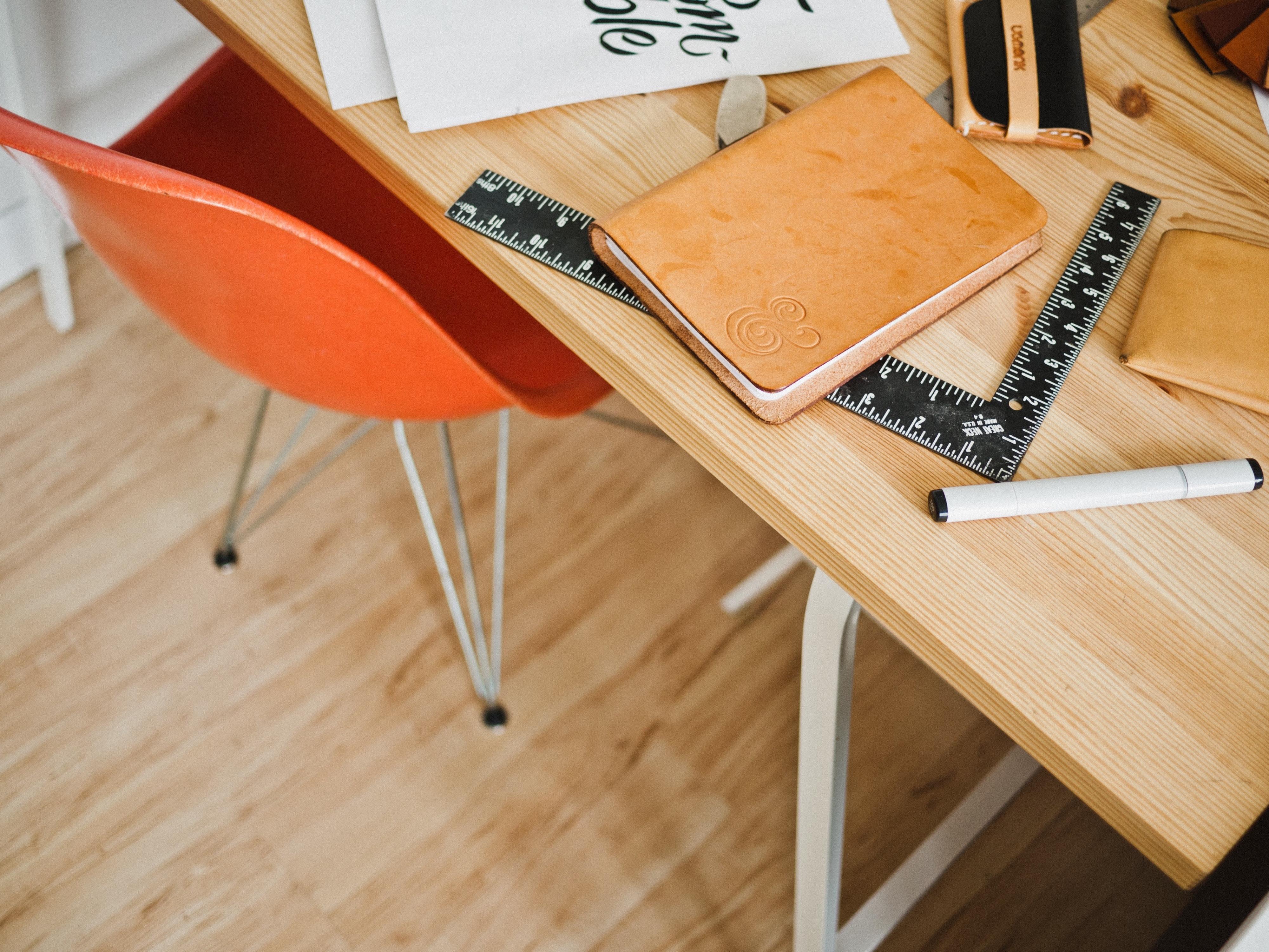 orange office chair under wooden desk
