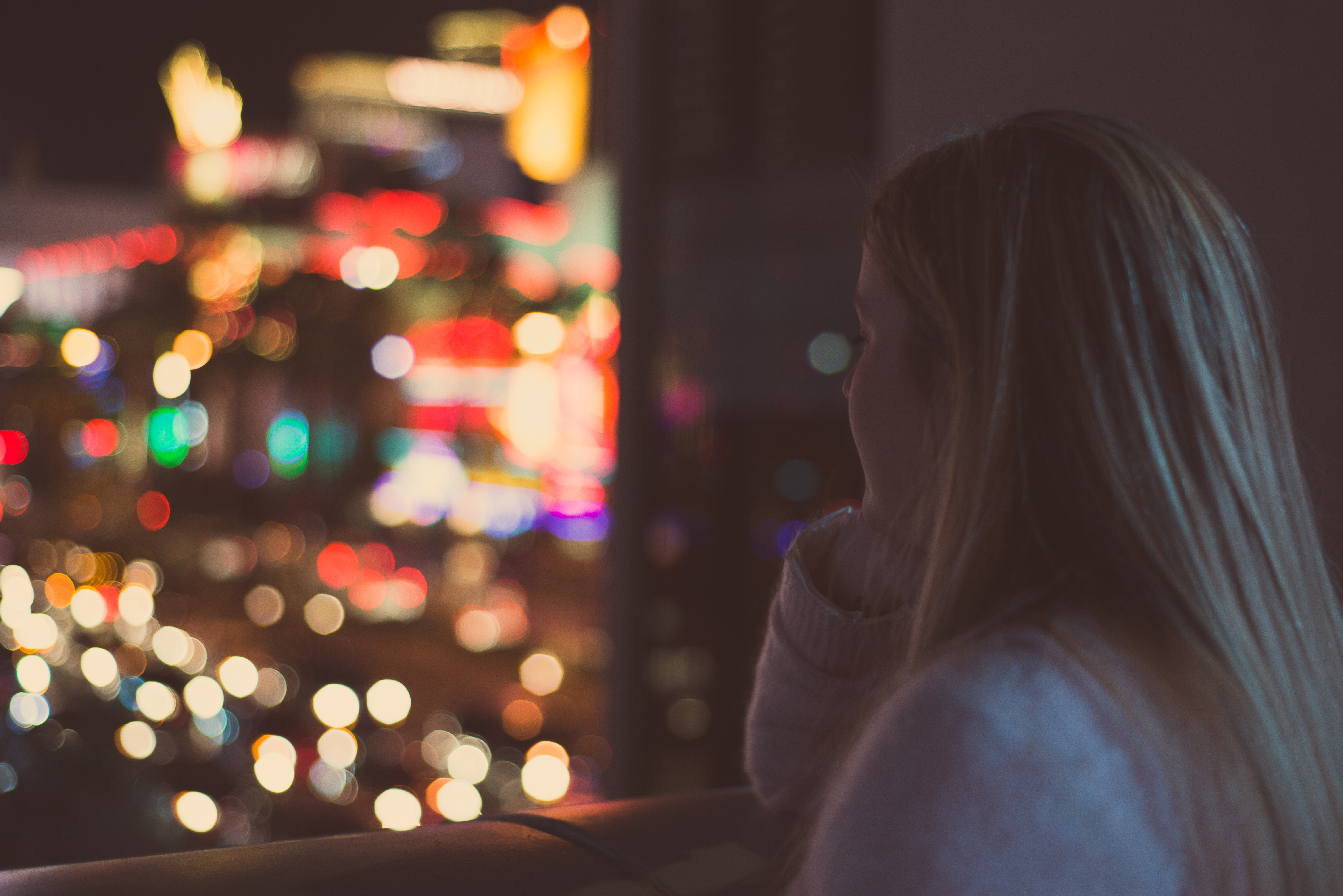 woman looking out window at city lights