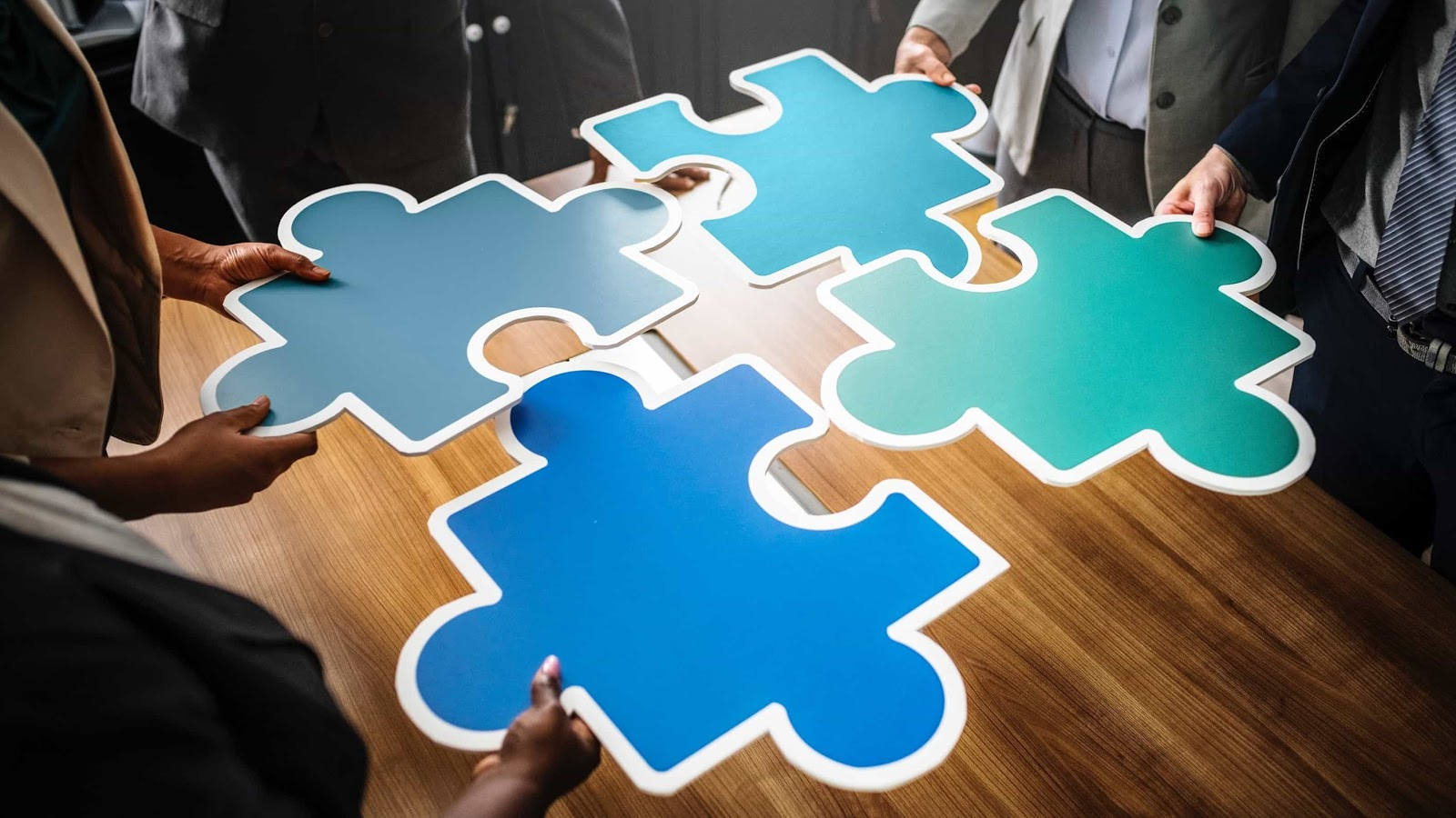 four people holding up giant puzzle pieces