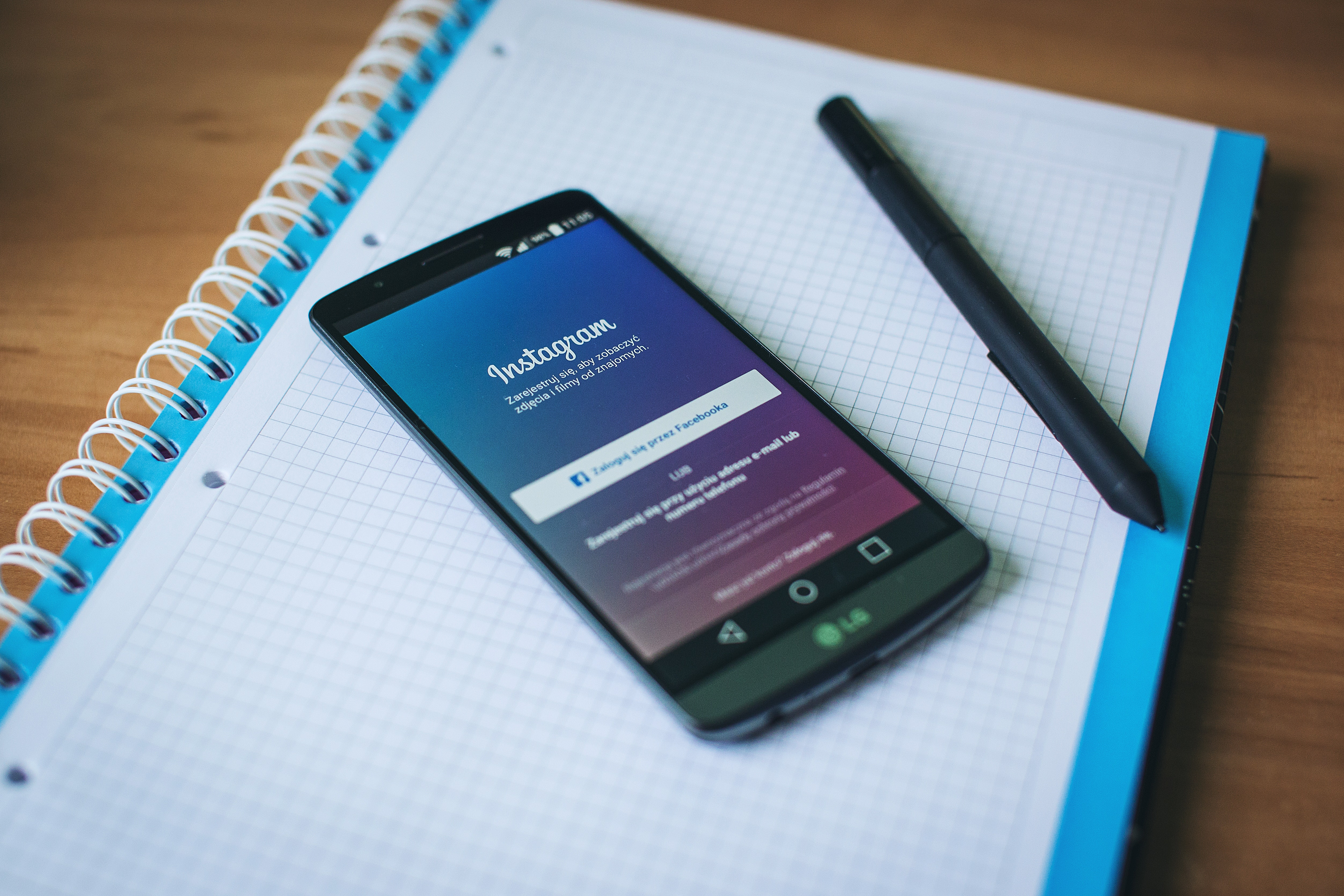 instagram open on phone on a notebook