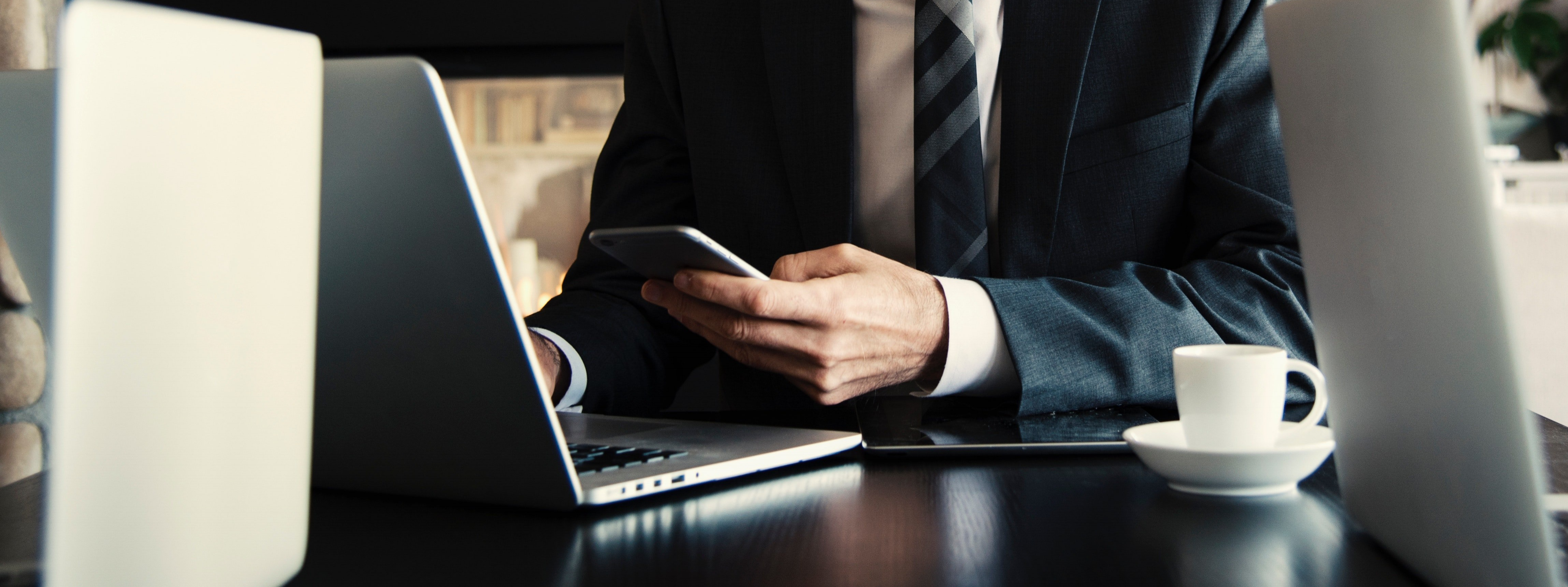 man-in-suit-on-phone-and-laptop-at-table-553114-edited