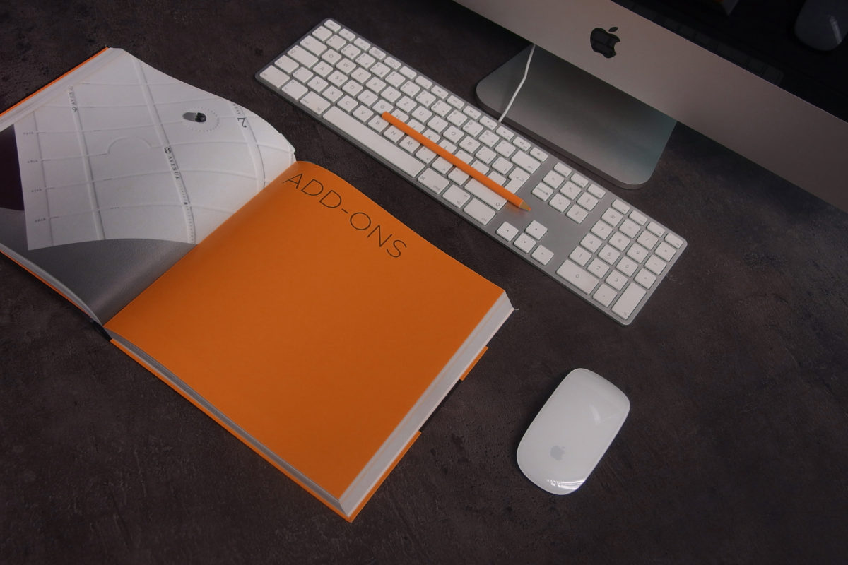 orange-book-for-understanding-HubSpot-pricing-in-front-of-computer