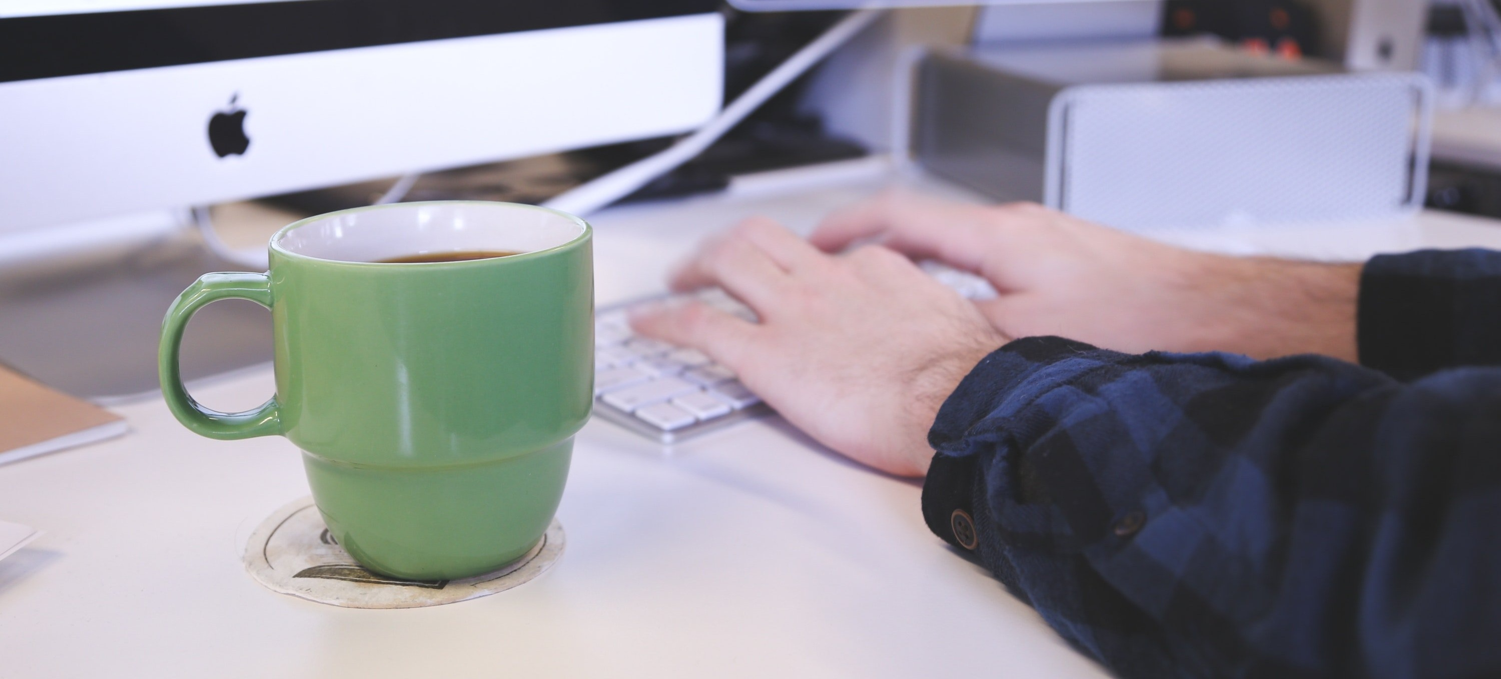 person-typing-on-keyboard-with-green-coffee-mug-293977-edited